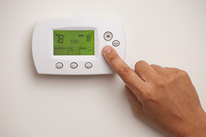 stock-photo-13056387-digital-thermostat-and-male-hand